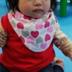 Mum2Mumのリバーシブルバンダナビブを着ける女の赤ちゃん